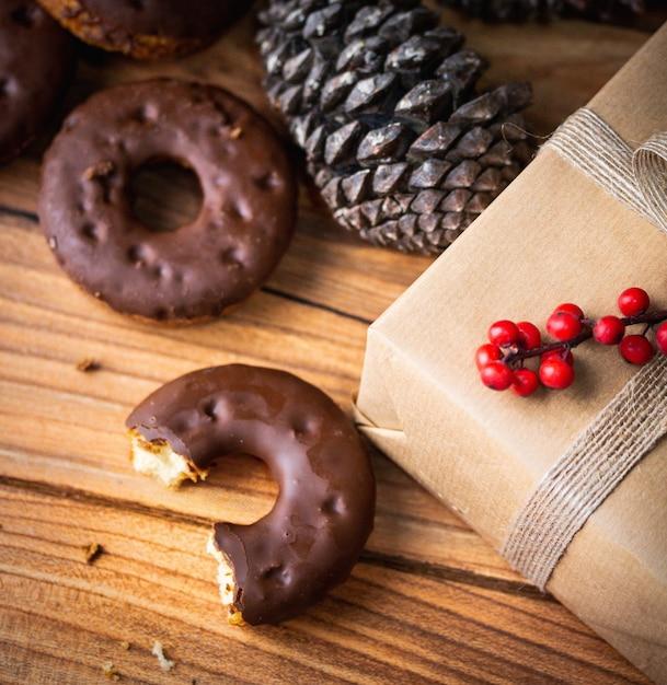 Hoge hoek close-up shot van een half opgegeten chocolade donut naast een ingepakt cadeau en een dennenappel Gratis Foto