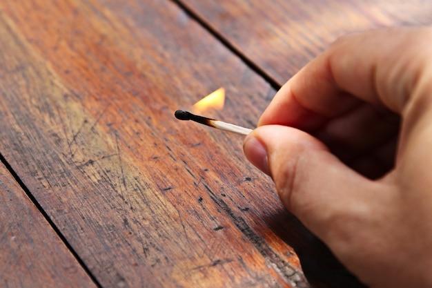 Hoge hoek close-up shot van een persoon met een brandende lucifer over een houten oppervlak Gratis Foto