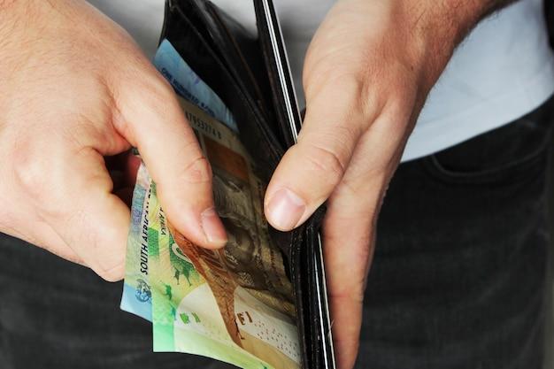 Hoge hoek close-up shot van een persoon wat geld steken in een lederen portemonnee Gratis Foto