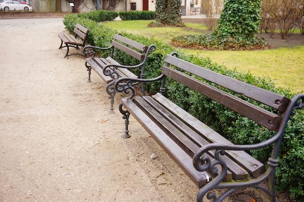 Hoge hoek close-up shot van houten banken in het park Gratis Foto