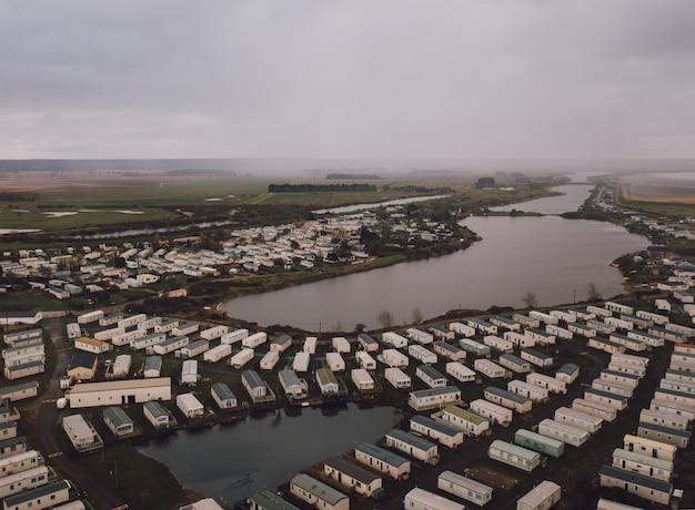 Hoge hoek die van de rechthoekige huizen op de velden is ontsproten door een mooie mistige vijver Gratis Foto