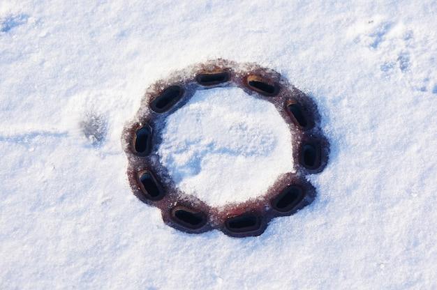 Hoge hoek die van een afvoer op de besneeuwde grond is ontsproten Gratis Foto