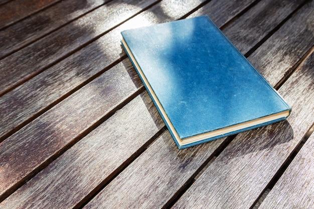 Hoge hoek die van een blauw boek op een houten oppervlakte is ontsproten Gratis Foto