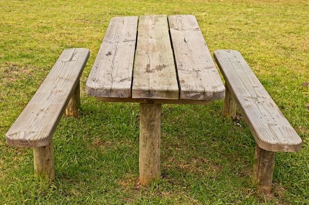 Hoge hoek die van een houten tafel en banken op het gras behandelde gebied is ontsproten Gratis Foto