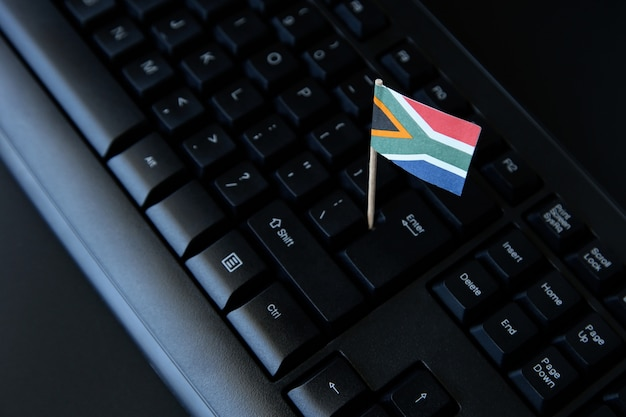 Hoge hoek die van een kleine vlag van zuid-afrika op een zwart computertoetsenbord is ontsproten Gratis Foto