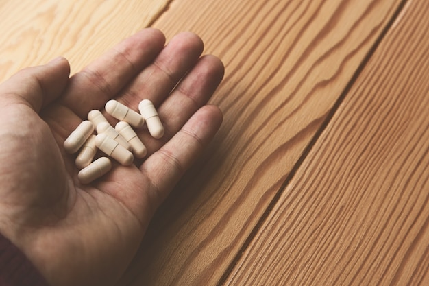Hoge hoek die van een persoon is ontsproten die een bos van witte capsules over een houten oppervlakte houdt Gratis Foto