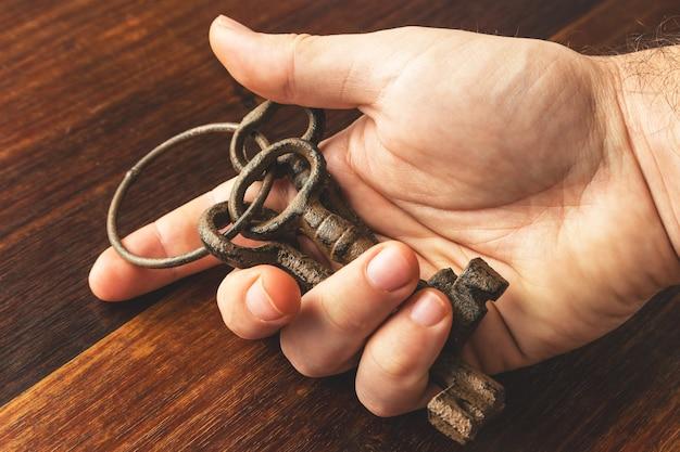 Hoge hoek die van een persoon is ontsproten die enkele oude en verroeste sleutels over een houten oppervlakte houdt Gratis Foto
