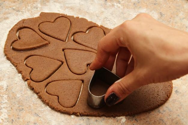 Hoge hoek die van een persoon is ontsproten die hartvormige koekjes maakt Gratis Foto