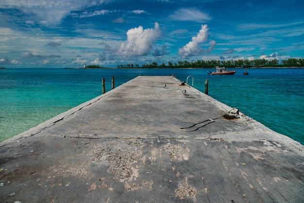 Hoge hoek die van een pier met een bewolkte blauwe hemel op de achtergrond is ontsproten Gratis Foto