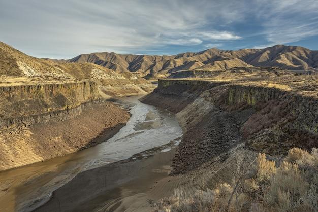 Hoge hoek die van een rivier in het midden van klippen met bergen in de verte onder een blauwe hemel is ontsproten Gratis Foto