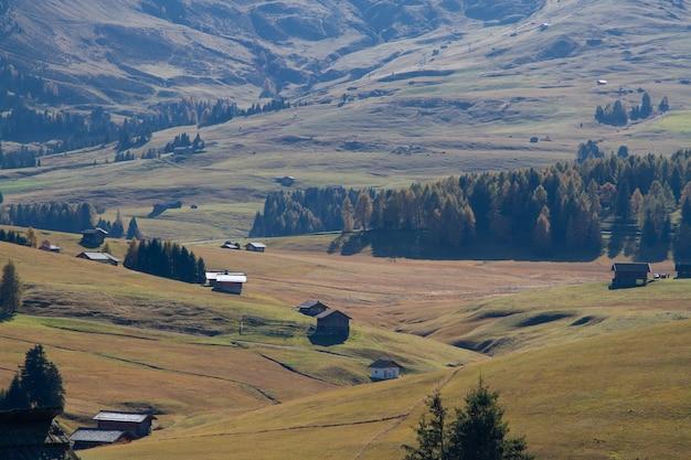 Hoge hoek die van gebouwen op met gras begroeide heuvels in dolomiet italië is ontsproten Gratis Foto