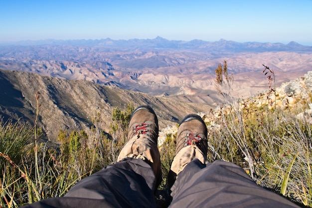 Hoge hoek die van iemands voeten is ontsproten die op de top van een heuvel boven een prachtige vallei zitten Gratis Foto