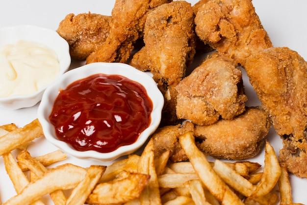 Hoge hoek friet en gebakken kip Gratis Foto