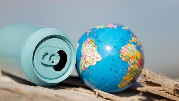 Hoge hoek frisdrankblikje naast kleine wereldbol Gratis Foto
