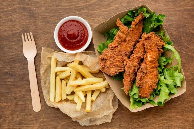 Hoge hoek gebakken kip en frietjes met ketchup Gratis Foto