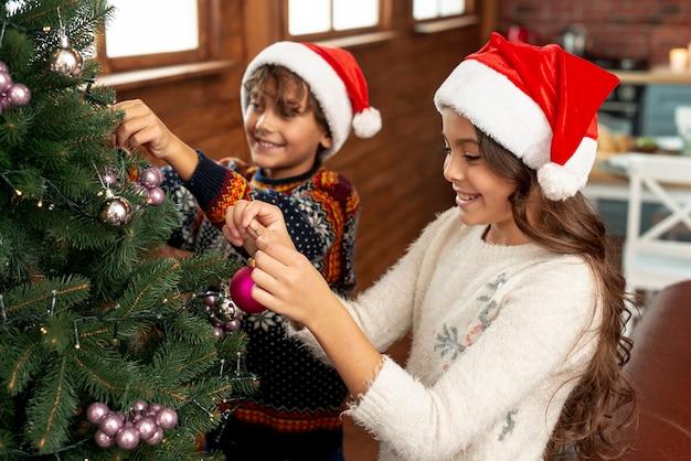 Hoge hoek gelukkige kinderen die de kerstmisboom verfraaien Gratis Foto