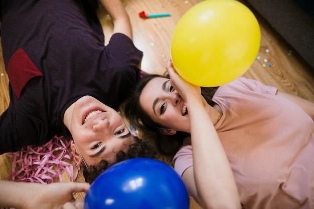 Hoge hoek gelukkige tieners die op de vloer leggen Gratis Foto