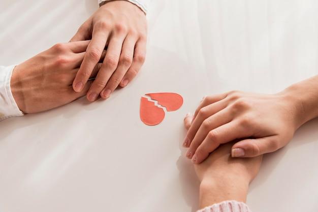 Hoge hoek handen met gebroken hart Gratis Foto