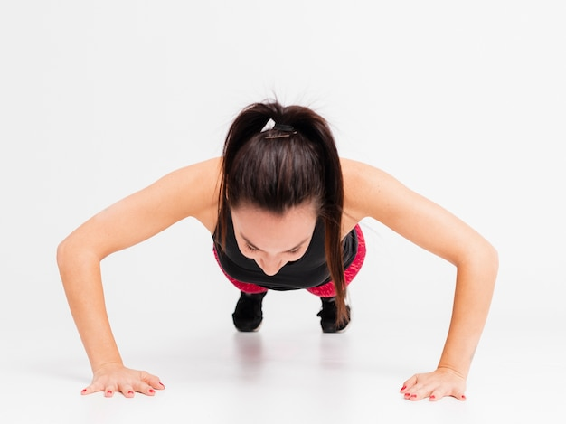 Hoge hoek jonge vrouw die opdrukoefeningen doet Gratis Foto