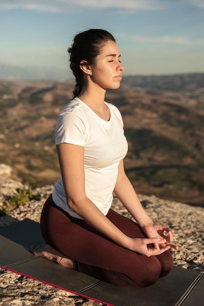 Hoge hoek jonge vrouw op mat mediteren Gratis Foto
