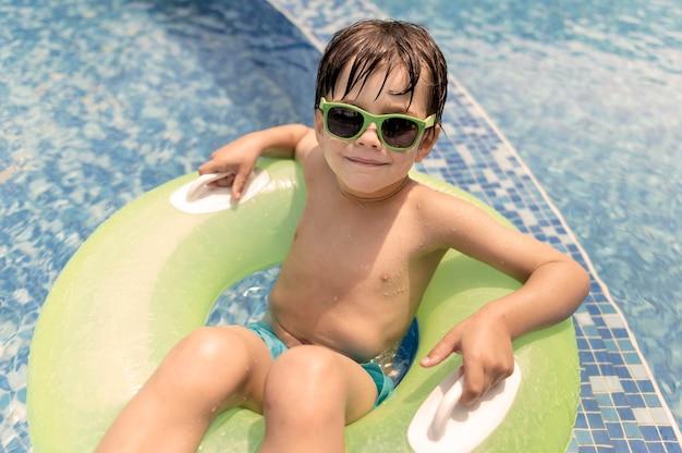 Hoge hoek jongen in zweven bij zwembad Gratis Foto