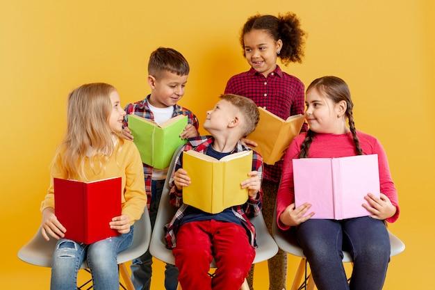 Hoge hoek kinderen met boeken kijken naar elkaar Gratis Foto