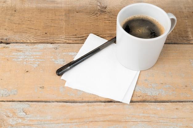 Hoge hoek koffiemok op houten achtergrond Gratis Foto
