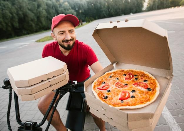 Hoge hoek levering man met geopende pizzadoos Gratis Foto