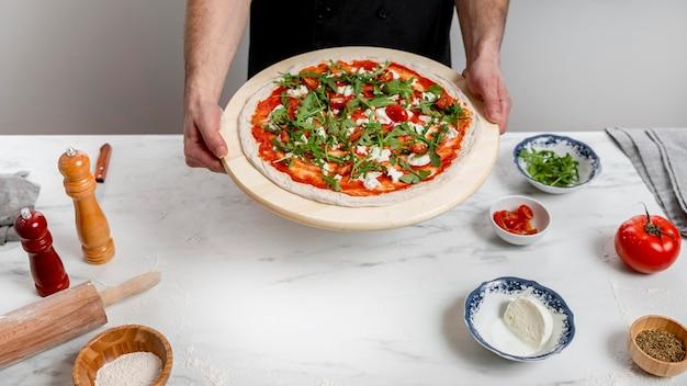 Hoge hoek man met snijplank met pizza Gratis Foto