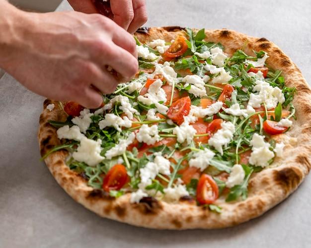 Hoge hoek man mozzarella zetten gebakken pizzadeeg met plakjes gerookte zalm Gratis Foto