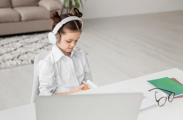 Hoge hoek meisje luistert naar haar leraar via een koptelefoon Gratis Foto