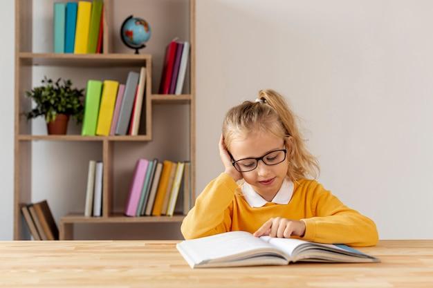 Hoge hoek meisje met bril lezen Gratis Foto