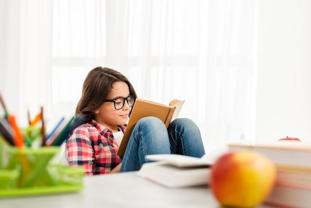 Hoge hoek meisje thuis lezen Gratis Foto
