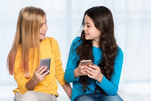 Hoge hoek meisjes met mobiel Gratis Foto