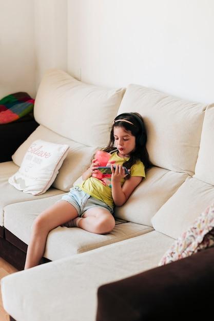 Hoge hoek meisjeszitting op laag met sap en smartphone Gratis Foto