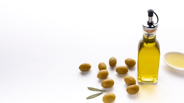 Hoge hoek olijfolie fles met gele olijven en kopie ruimte Gratis Foto