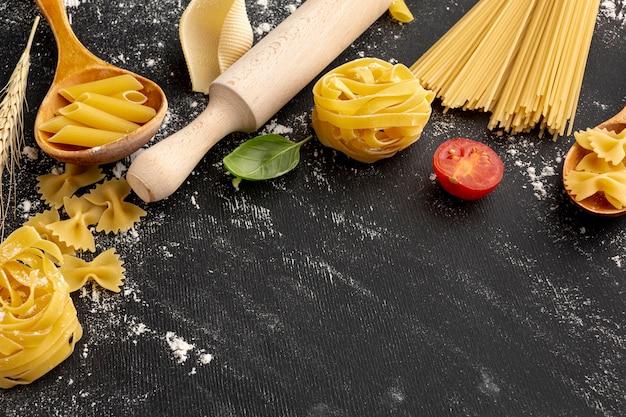 Hoge hoek ongekookte pasta met deegrol en kopie ruimte Gratis Foto