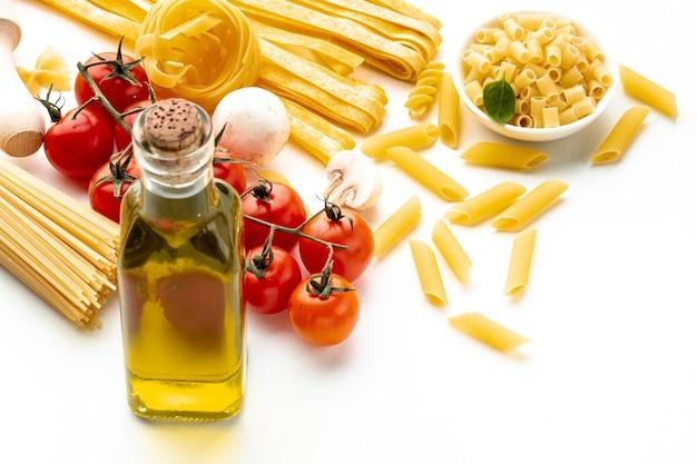 Hoge hoek ongekookte pasta met tomaten en olijfolie Gratis Foto