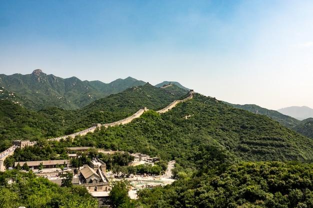 Hoge hoek opname van de beroemde grote muur van china, omringd door groene bomen in de zomer Gratis Foto