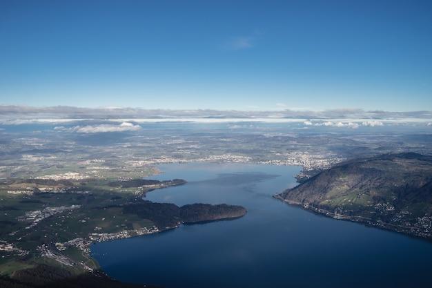 Hoge hoek opname van het meer van zug in zwitserland onder een heldere blauwe hemel Gratis Foto