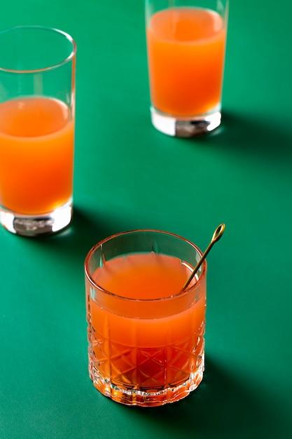 Hoge hoek oranje drankjes op groene achtergrond Gratis Foto