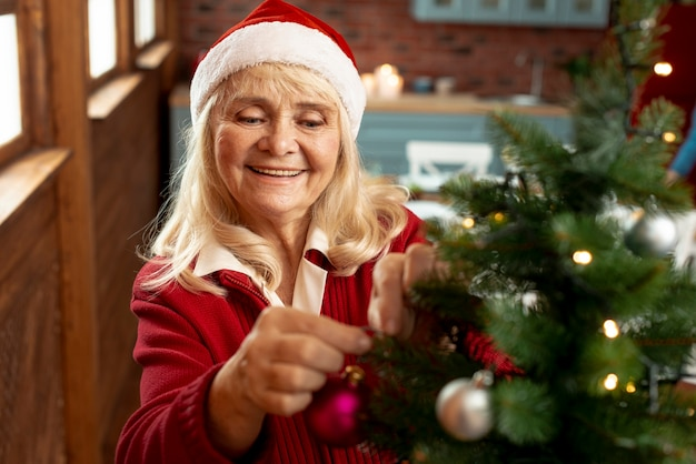 Hoge hoek oude vrouw die de kerstmisboom verfraait Gratis Foto