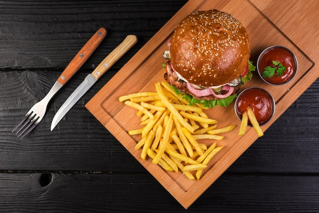 Hoge hoek rundvleesburger met friet en ketchupsaus Gratis Foto