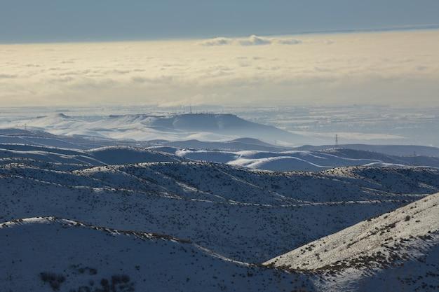 Hoge hoek schot van besneeuwde bergen met een blauwe bewolkte hemel overdag Gratis Foto