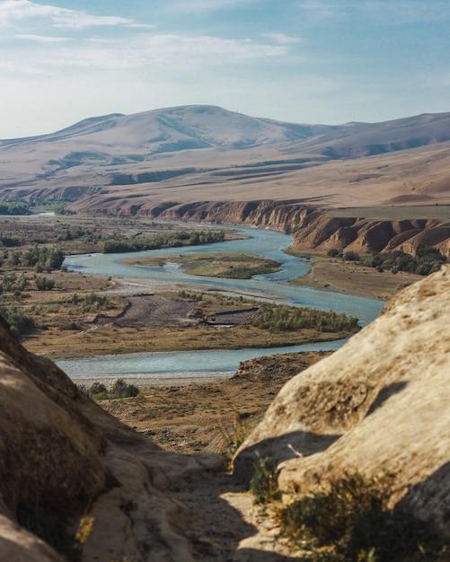 Hoge hoek schot van een bochtige rivier omgeven door hoge bergen onder de bewolkte hemel Gratis Foto