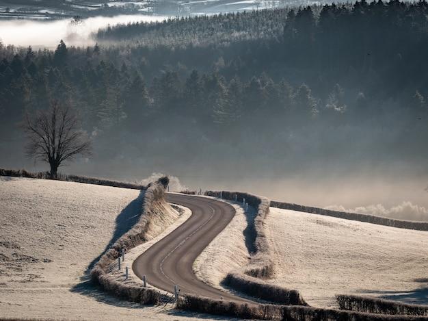 Hoge hoek schot van een bochtige weg in het midden van besneeuwde velden met beboste heuvels Gratis Foto