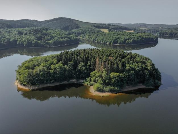 Hoge hoek schot van een kust bedekt met bomen in de zee met een heldere blauwe hemel Gratis Foto