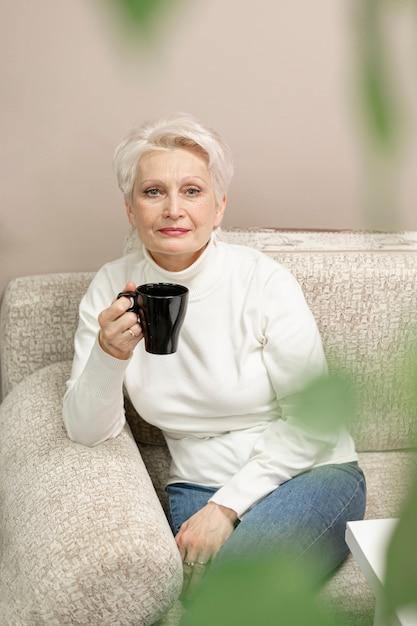 Hoge hoek senior vrouw genieten van kopje koffie Gratis Foto