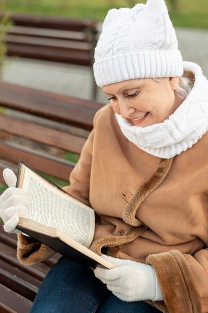 Hoge hoek senior vrouwelijke lezing buiten Gratis Foto