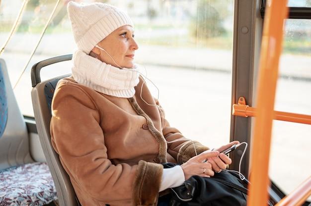 Hoge hoek senior vrouwelijke luisteren muziek Gratis Foto